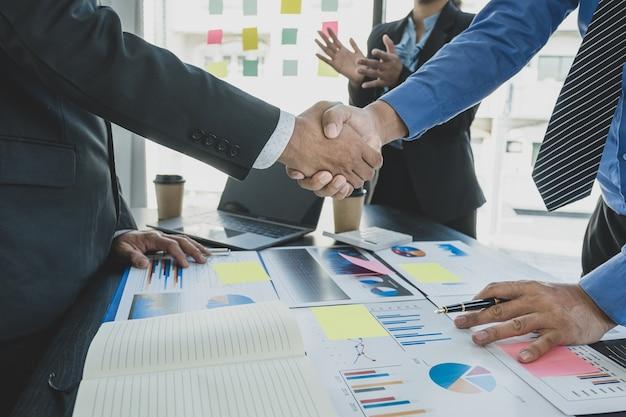 Apretón de manos después de la reunión del equipo de mujeres empresarias y empresarios para planificar estrategias para aumentar los ingresos comerciales