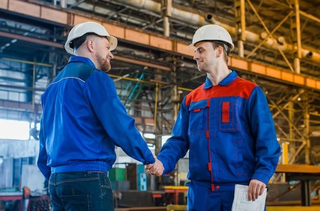 Apretón de manos de dos hombres de ingenieros con cascos blancos.