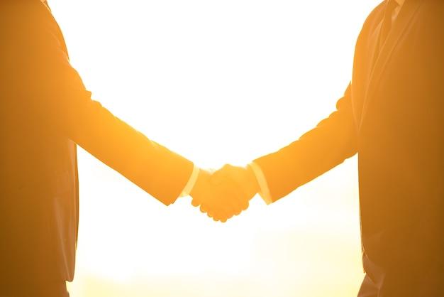 El apretón de manos de dos hombres de negocios en el fondo del sol brillante