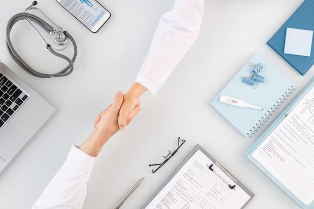 Apretón de manos de dos jóvenes médicos exitosos con batas blancas que se saludan en el lugar de trabajo con documentos y otros suministros médicos