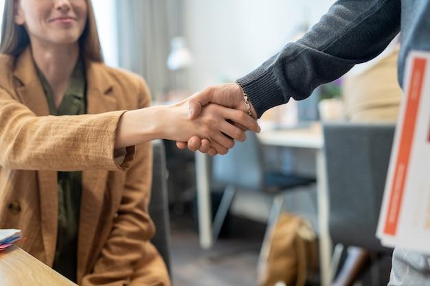 Apretón de manos de dos jóvenes oficinistas contra el lugar de trabajo