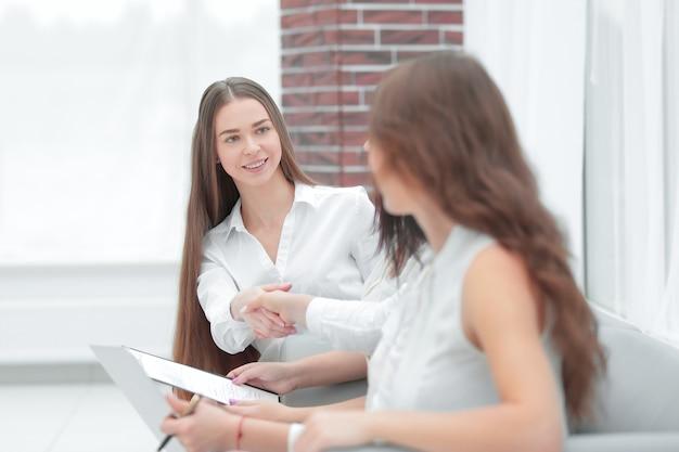 Apretón de manos de dos mujeres de negocios sentadas en el pasillo de la oficina.