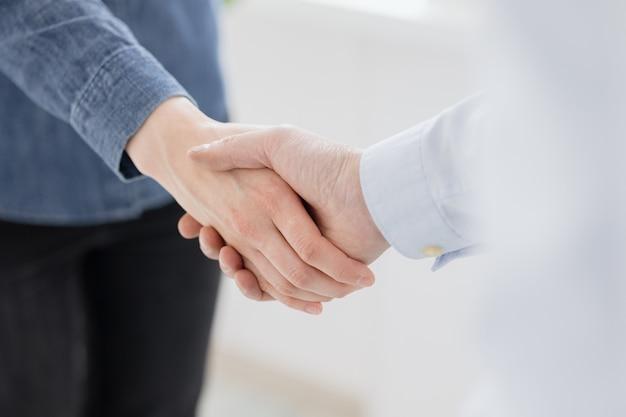 Un apretón de manos de dos personas, un hombre y una mujer saludan a los socios comerciales