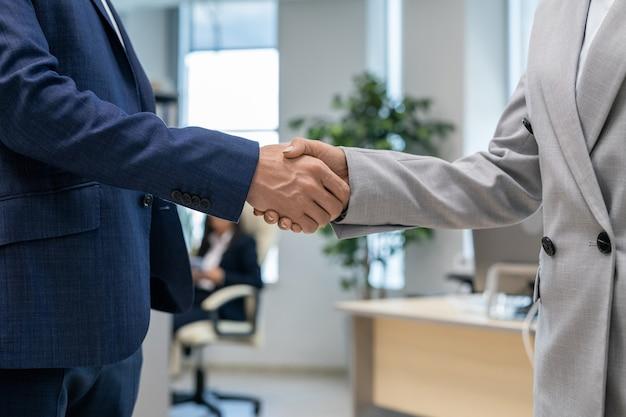 Apretón de manos de dos socios comerciales jóvenes en entorno de oficina
