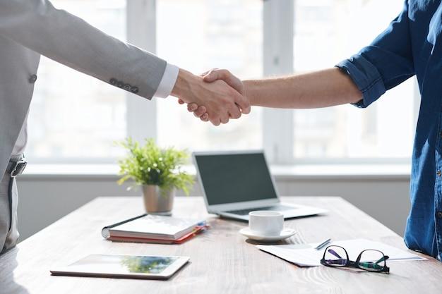 Apretón de manos de dos socios comerciales jóvenes sobre el escritorio con suministros de oficina después de firmar el contrato en la reunión