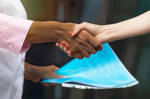 '' apretón de manos empresarial entre mujeres afroamericanas negras y europeas blancas