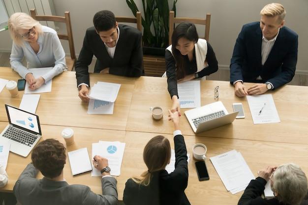 Apretón de manos de las empresarias asiáticas y caucásicas en la reunión de grupo, visión superior