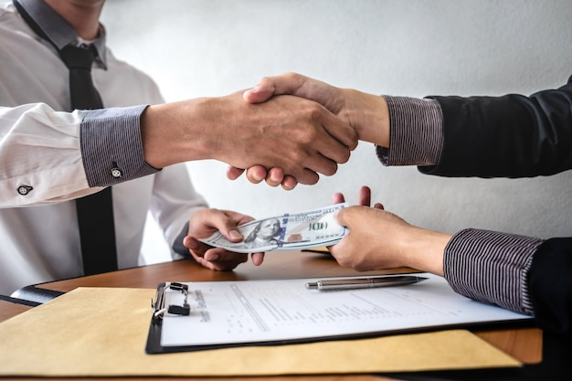 Apretón de manos de empresario con dinero de billetes de dólar en manos de mientras dar contrato de éxito