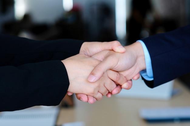 Apretón de manos de empresario y empresaria en reunión corporativa de asociación