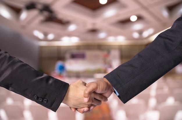 Apretón de manos entre un empresario y una empresaria.