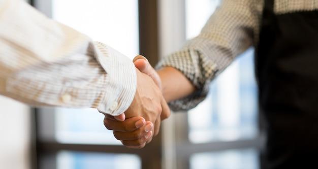 Apretón de manos de empresario con pareja para el éxito