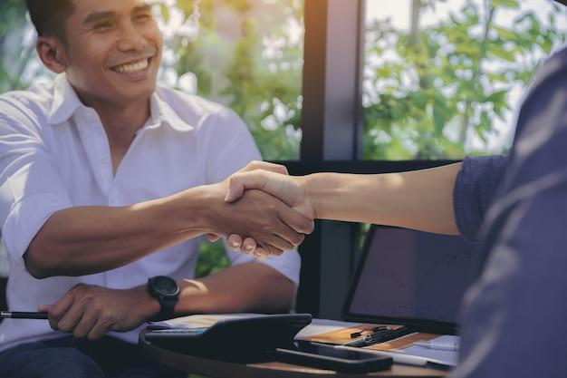 Apretón de manos de empresario en reunión de negocios después de negociaciones con socios comerciales