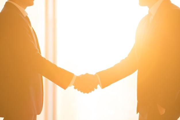 El apretón de manos de los empresarios en el fondo del sol brillante