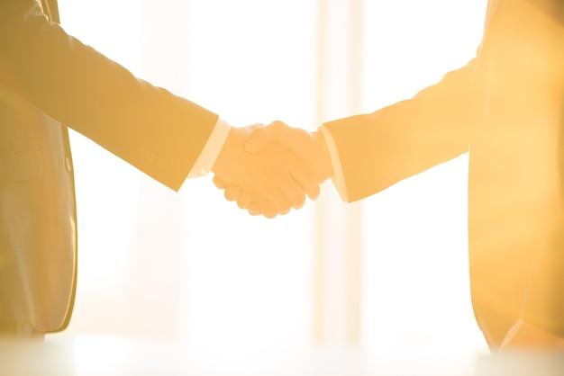 El apretón de manos de los empresarios en el fondo soleado