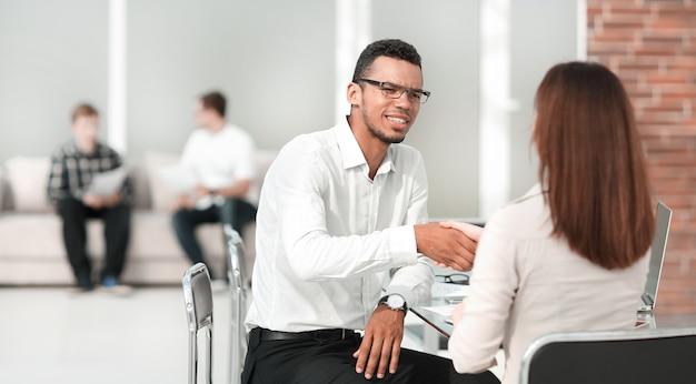Apretón de manos de empresarios en la oficina del banco