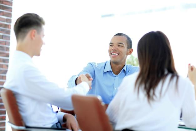 Apretón de manos, empresarios, sentado, en, un, escritorio., el, concepto empresarial