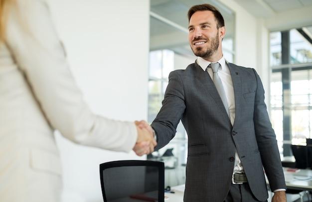 Apretón de manos exitoso hombre de negocios y empresaria en trajes en el fondo de la oficina. concepto de asociación empresarial.