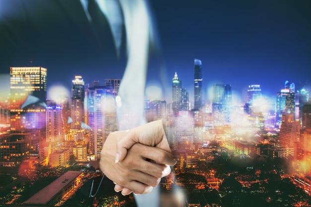 Apretón de manos de la exposición doble en un fondo de la ciudad, concepto del negocio.