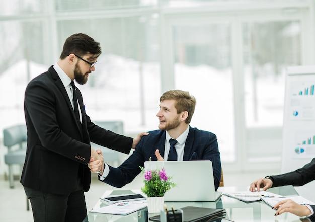 Apretón de manos entre el gerente y el cliente antes de firmar un contrato.