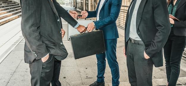 Apretón de manos del grupo de empresarios en la ciudad, equipo de negocios