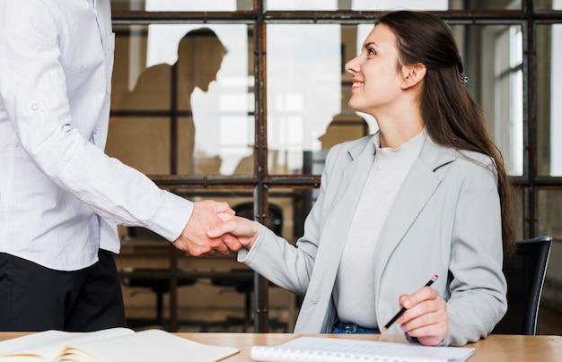 Apretón de manos hermoso de la empresaria con su colega