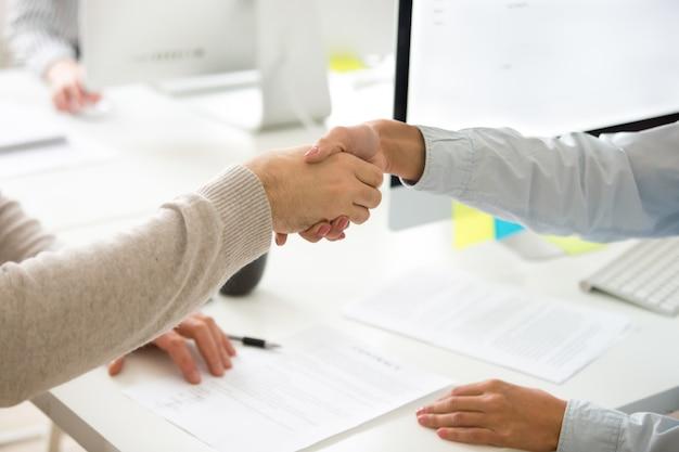 Apretón de manos de hombre y mujer después de firmar contrato comercial, primer plano