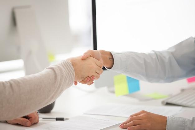 Apretón de manos del hombre de negocios y de la empresaria después de firmar el contrato o la negociación acertada
