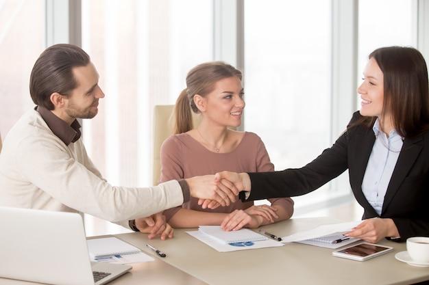 Apretón de manos del hombre de negocios y de la empresaria en la reunión de negocios que se sienta en oficina