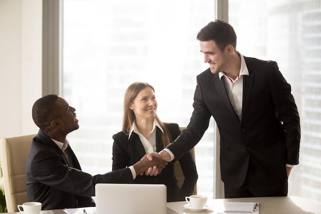 Apretón de manos de hombres de negocios alegres afroamericanos y caucásicos en