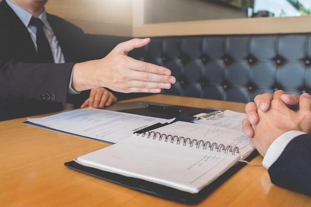 Apretón de manos del jefe y del empleado del negocio después de negociaciones o de entrevista exitosas.