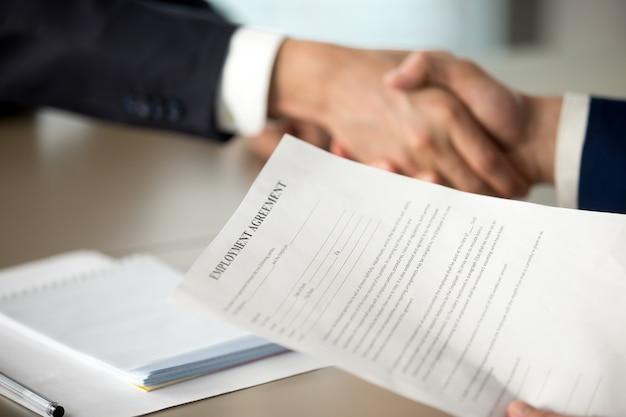 Apretón de manos de jefe y oferta de contrato de trabajo.
