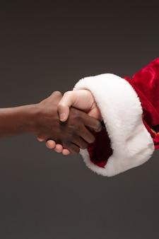 El apretón de manos de la mano de santa claus y la mano del hombre africano. concepto de feliz navidad