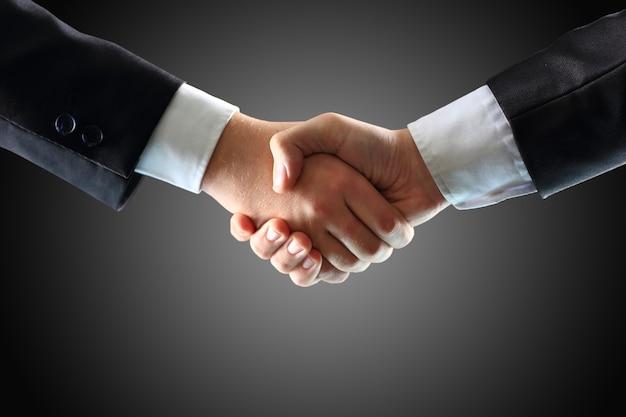 Apretón de manos - mano sujetando sobre fondo negro