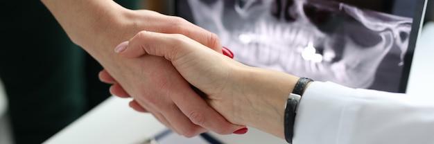 Apretón de manos médico dentista y paciente cerca de tomografía computarizada de mandíbula en clínica con éxito
