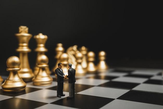 Apretón de manos miniatura del hombre de negocios en el tablero de ajedrez con el fondo del ajedrez del oro.