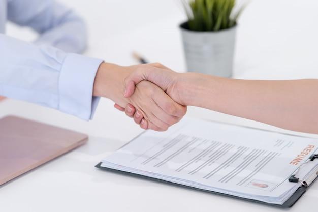 Apretón de manos de mujer después de aceptado en una entrevista de trabajo.