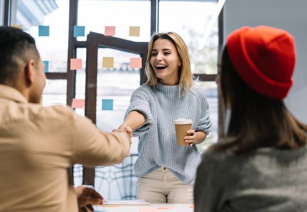 Apretón de manos de mujer de negocios con socio comercial, trato exitoso. equipo trabajando juntos, planeando startup, colaborando