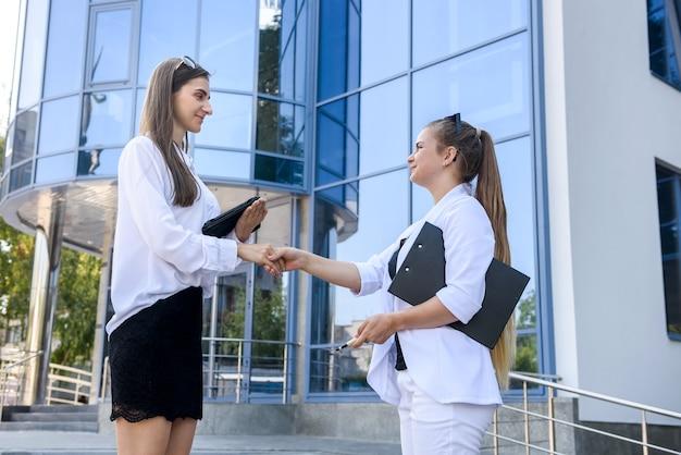 Apretón de manos de mujeres hermosas cerca de la entrada en el edificio de oficinas