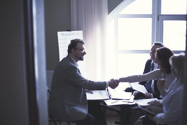 Apretón de manos de mujeres y hombres de negocios cerca del escritorio en la oficina