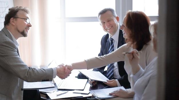Apretón de manos de mujeres de negocios y hombres de negocios cerca del escritorio en la oficina