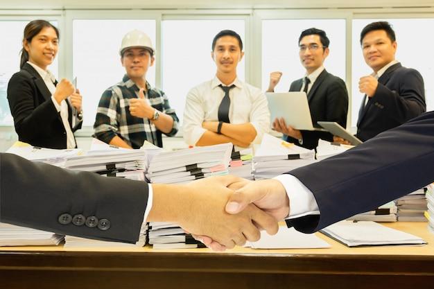 Apretón de manos del negocio acertado con la pila de papeleo y el grupo de trabajo en equipo en fondo.