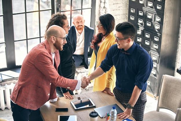 Apretón de manos de negocios en una reunión o negociación en la oficina. los socios están satisfechos porque firman contratos o documentos financieros. enfoque selectivo.