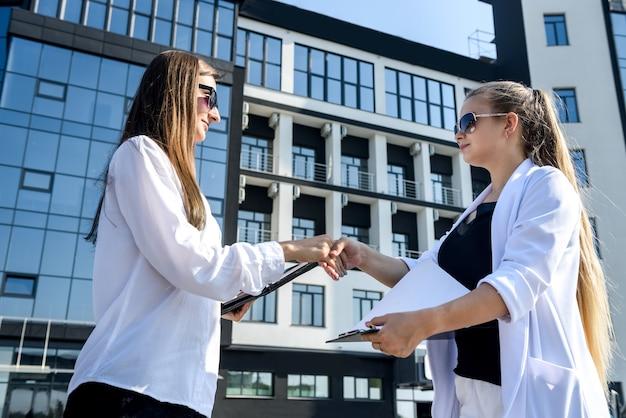 Apretón de manos de socios comerciales antes del edificio de oficinas