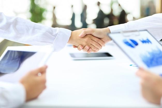 Apretón de manos de socios comerciales después de la conclusión de un contrato exitoso en el lugar de trabajo