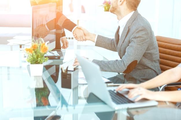 Apretón de manos de socios comerciales en el fondo del escritorio