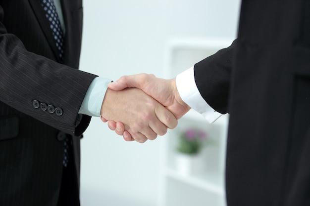 Apretón de manos de socios comerciales en oficina borrosa