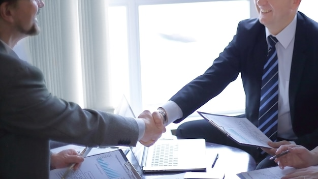 Apretón de manos de socios comerciales senior en el escritorio de la oficina