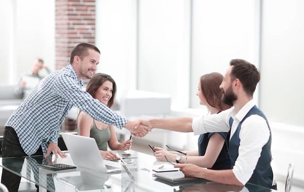 Apretón de manos de socios comerciales sobre el escritorio en la oficina concepto de cooperación.