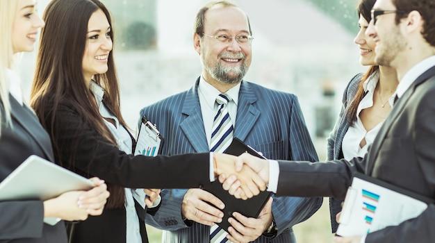 Apretón de manos de socios financieros y abogados de la empresa.