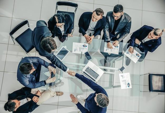 Apretón de manos de vista superior de empleados felices en una reunión de trabajo